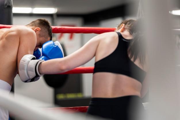 Männliche und weibliche boxer, die sich im ring gegenüberstehen