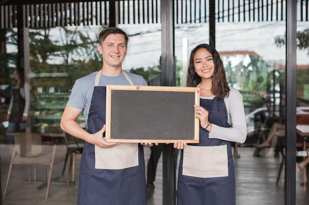 Männliche und weibliche cafébesitzer stehen stolz vor ihrem café oder café