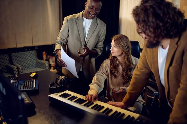 Männliche und weibliche darsteller, aufnahmestudio-interieur im hintergrund. synthesizer und audiomixer, musikerarbeitsplatz, kreativer prozess