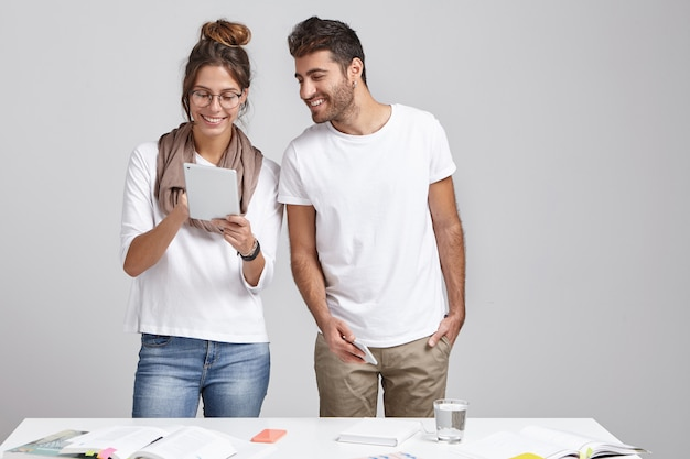 Männliche und weibliche designer oder wissenschaftliche mitarbeiter stehen in der nähe des arbeitsplatzes in einem gemütlichen büro.