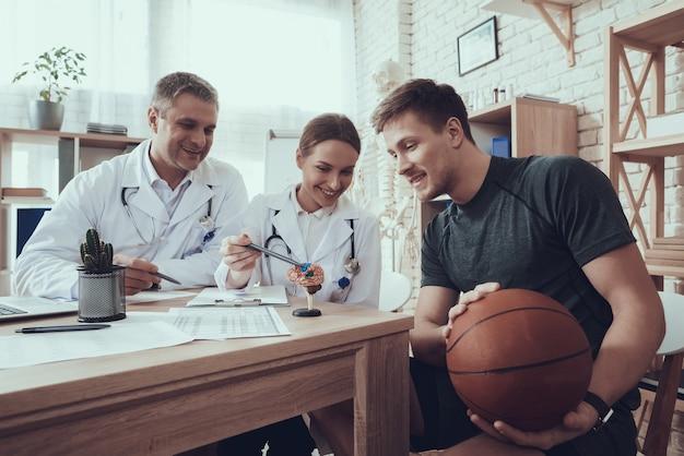 Männliche und weibliche doktoren in der klinik mit basketballspieler.