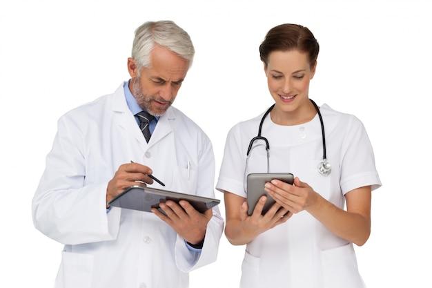 Männliche und weibliche doktoren mit digitalen tabletten