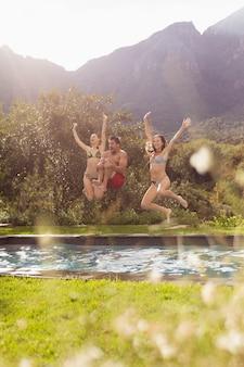 Männliche und weibliche freunde, die in swimmingpool am hinterhof springen