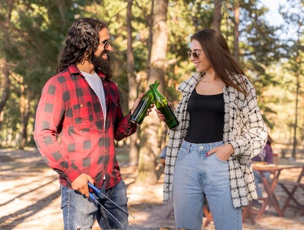 Männliche und weibliche freunde, die mit bier über dem grill rösten