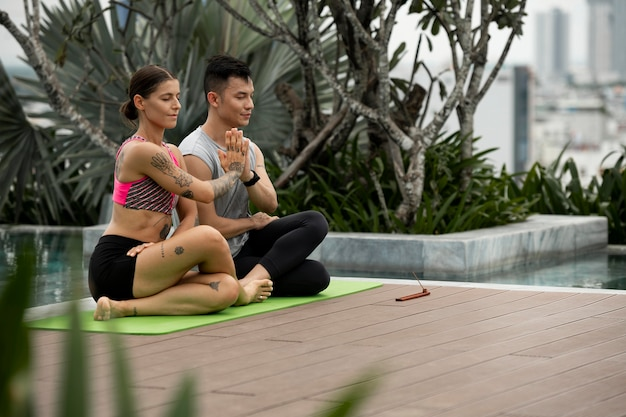 Männliche und weibliche freunde, die yoga praktizieren
