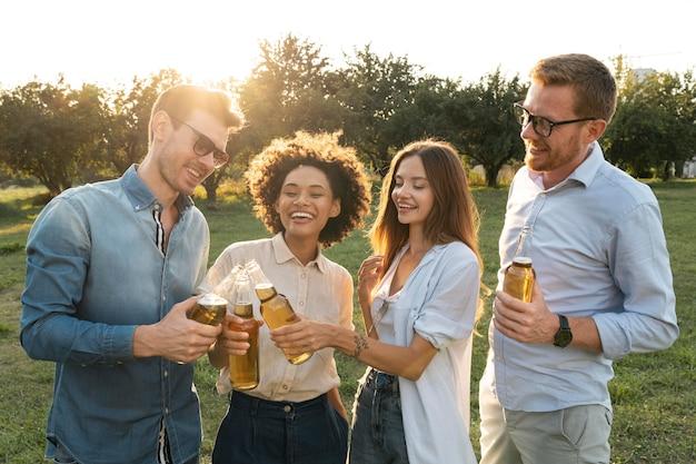 Männliche und weibliche freunde verbringen zeit zusammen im freien und trinken bier