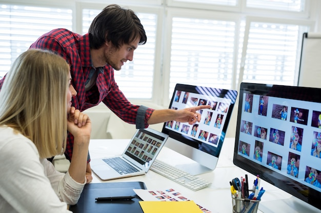 Männliche und weibliche grafikdesigner über computer interagieren