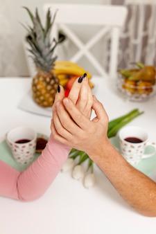 Männliche und weibliche hände, die an tabelle halten