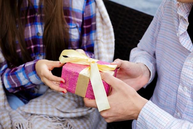Männliche und weibliche hände, die eine rosa geschenkbox halten.