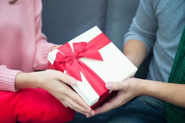 Männliche und weibliche hände, die goldenen kasten des geschenks mit rotem band halten. geschenk zum geburtstag, valentinstag, weihnachten