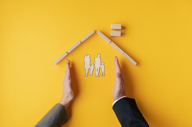 Männliche und weibliche hände, die platziert werden, um ein haus für papier geschnittene silhouette einer familie in einem konzeptuellen bild zu bilden.