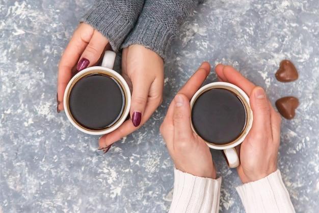 Männliche und weibliche hände, die tasse kaffees halten. selektiver fokus