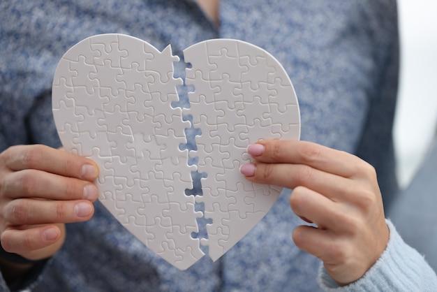 Männliche und weibliche hände, die weißes herz aus puzzle-nahaufnahme verbinden