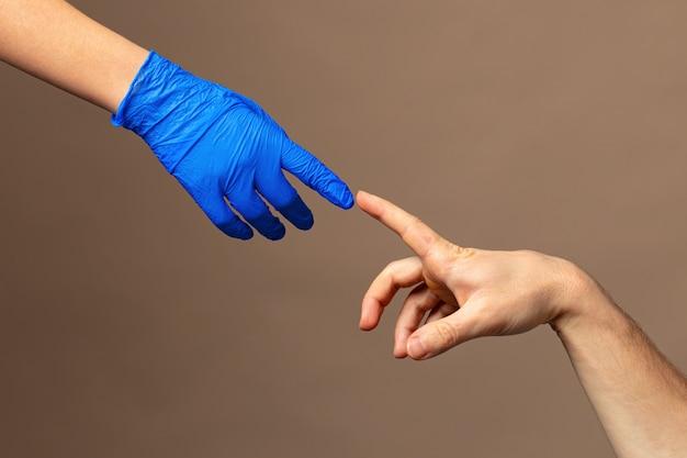 Männliche und weibliche hände in medizinischen handschuhen strecken sich zueinander. hilfekonzept. nahansicht