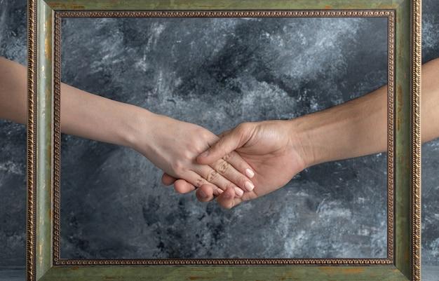 Männliche und weibliche händeschütteln in der mitte des bilderrahmens.