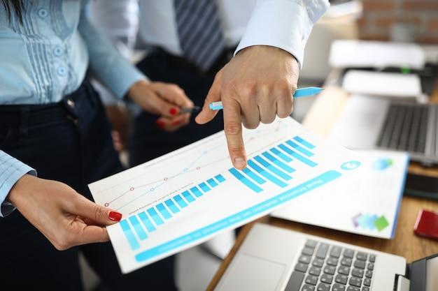 Männliche und weibliche hand, die diagramme mit geschäftsindikatoren im amt hält. planungs- und entwicklungskonzept für kleine und mittlere unternehmen