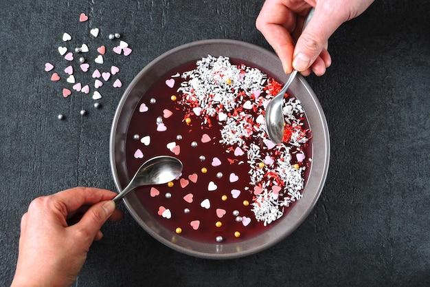Männliche und weibliche hand mit löffeln essen rote marmelade aus der schüssel, dekoriert zum valentinstag.