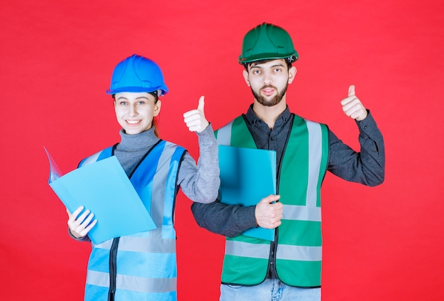 Männliche und weibliche ingenieure im helm, die positive handzeichen zeigen.