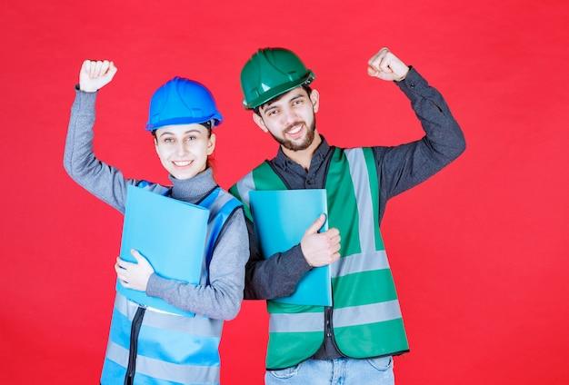 Männliche und weibliche ingenieure mit helm, der berichtsordner hält und erfolgreiches handzeichen zeigt.