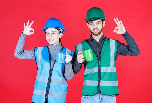 Männliche und weibliche ingenieure mit helm, der blaue und grüne becher hält und zufriedenheitszeichen zeigt.