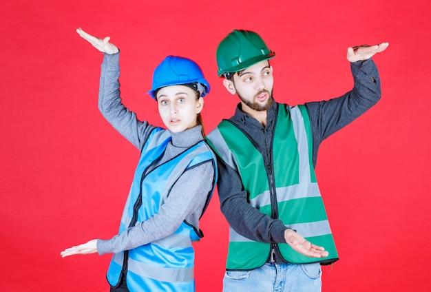 Männliche und weibliche ingenieure mit helm, der die größe eines objekts anzeigt.