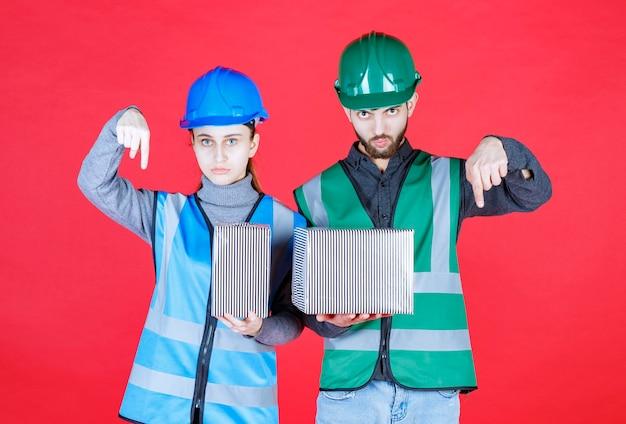 Männliche und weibliche ingenieure mit helm, der silberne geschenkboxen hält und jemanden bemerkt oder anruft, um es zu nehmen.