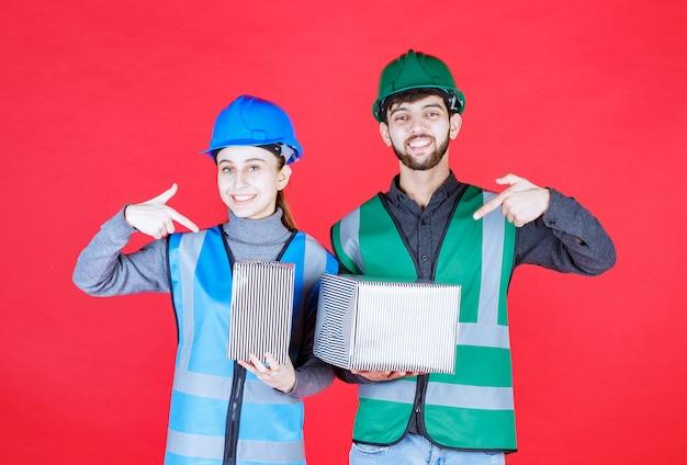 Männliche und weibliche ingenieure mit helm, der silberne geschenkboxen hält.
