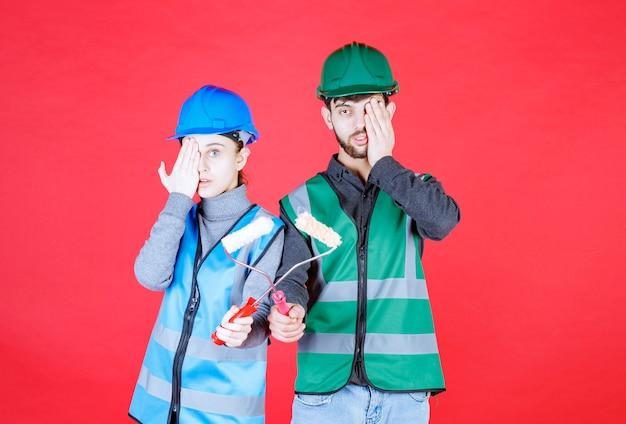 Männliche und weibliche ingenieure mit helm halten trimmrollen und sehen begeistert und gestresst aus.
