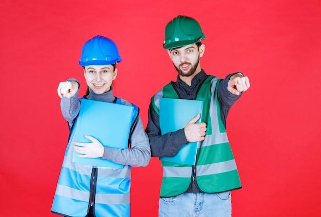 Männliche und weibliche ingenieure mit helmen, die blaue ordner halten und auf jemanden in der nähe zeigen.