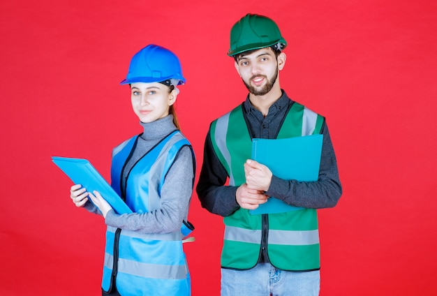 Männliche und weibliche ingenieure mit helmen, die blaue ordner halten.