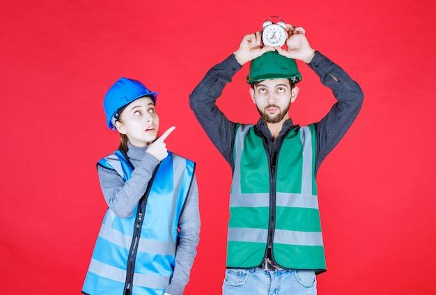 Männliche und weibliche ingenieure mit helmen, die einen wecker halten, sehen erschrocken aus, da sie zu spät kommen.