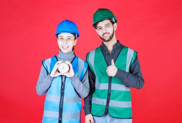 Männliche und weibliche ingenieure mit helmen, die einen wecker halten und positives handzeichen zeigen.