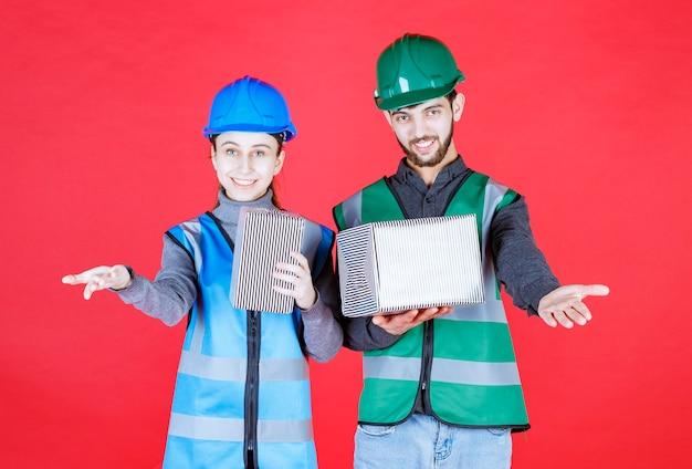 Männliche und weibliche ingenieure mit helmen, die silberne geschenkboxen halten und jemanden anrufen und einladen, sie zu empfangen.
