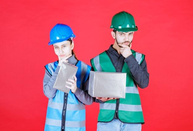 Männliche und weibliche ingenieure mit helmen, die silberne geschenkboxen halten und verwirrt und nachdenklich aussehen.