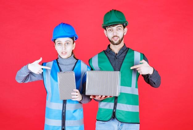 Männliche und weibliche ingenieure mit helmen, die silberne geschenkboxen halten.