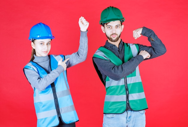 Männliche und weibliche ingenieure mit helmen fühlen sich kraftvoll und positiv.