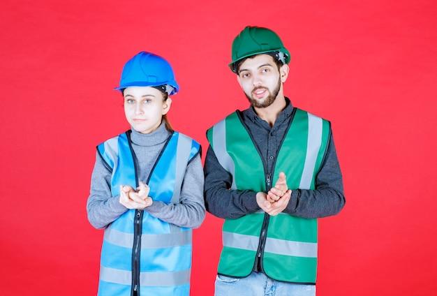 Männliche und weibliche ingenieure mit helmen geben ruhige und neutrale posen.