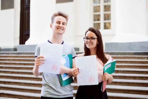 Männliche und weibliche jugendliche, die vor der universität stehen, die ausgezeichnete ergebnisse der aufnahmeprüfung zeigt, glücklich, studenten einer populären universität zu werden und stark zu studieren