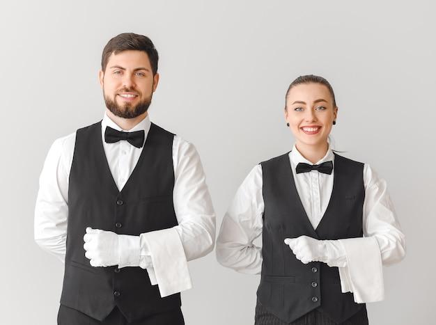 Männliche und weibliche kellner auf grauem hintergrund