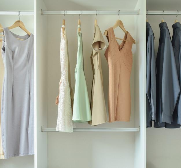Männliche und weibliche kleidung, die an den aufhängern in der garderobe hängt