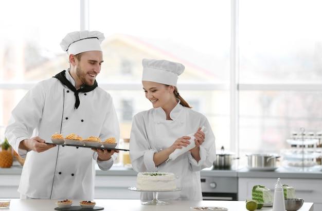 Männliche und weibliche köche, die an der küche arbeiten