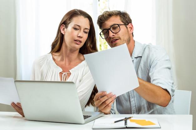 Männliche und weibliche kollegen, die dokument im büro besprechen