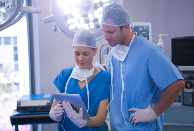Männliche und weibliche krankenschwester, die digitales tablett im operationssaal verwendet