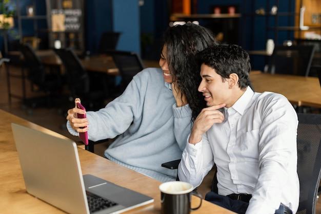 Männliche und weibliche mitarbeiter lächeln, während sie einen videoanruf haben