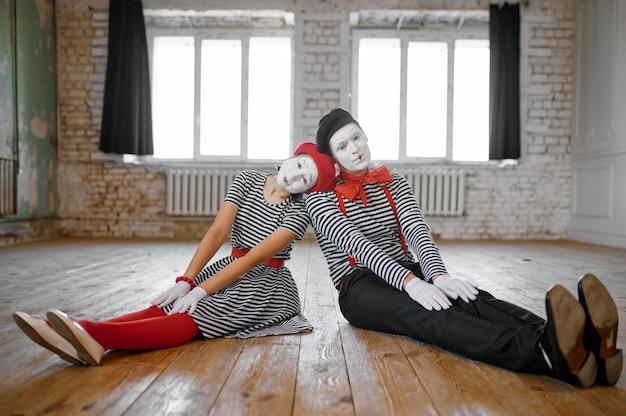 Männliche und weibliche pantomimen, die auf dem boden sitzen, liebespaarparodieszene, komödie