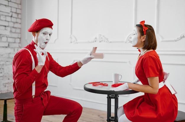 Männliche und weibliche pantomimen, szene mit geschenk