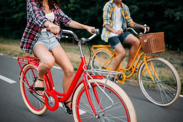 Männliche und weibliche personen, die auf retro-fahrrädern fahren. paar auf vintage-fahrrädern. junger mann und frau auf alten zyklen