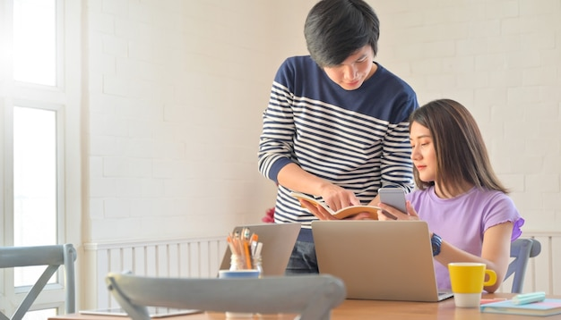 Männliche und weibliche schüler diskutieren projekte, um lehrern die arbeit mit smartphones und laptops zu ermöglichen.