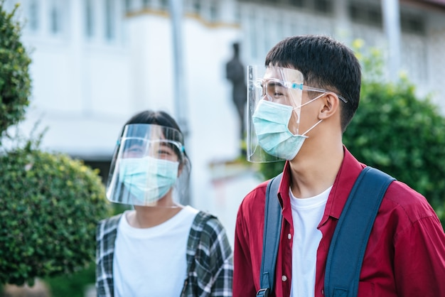 Männliche und weibliche schüler tragen gesichtskälte und masken. gehen sie den fußweg entlang