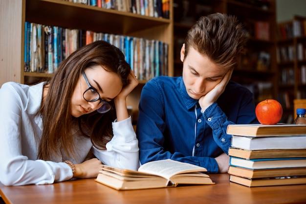 Männliche und weibliche studenten, die bücher lesen